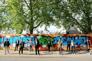 """Zur Einweihung der """"Wand der Solidarität im Hasenleiser"""" griffen auch Erster Bürgermeister Jürgen Odszuck (5.v.l.), Stadtteilvereinsvorsitzender Hans-Jürgen Fuchs (4.v.r.) sowie Rebecca Ramirez (3.v.l.) und Sarah Labusga (r.) vom Quartiersmanagement gerne zum Marker"""